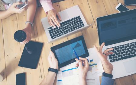 Giovane squadra di affari Brainstorming Sala riunioni Process.Coworkers avvio Marketing Project.Creative persone che fanno grandi decisioni lavoro legno Table.Tablet Laptop I grafici Diagramma Screen.Blurred Sfondo