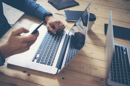 insider: Businessman Insider working wood table laptop Modern Interior Design Loft Office.Man Work Coworking Studio,Use Notebook,Typing Touch Screen Smartphone.Blurred Background.Creative Business Startup