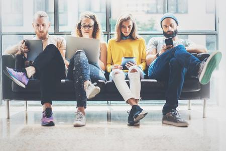 그룹 성인 hipsters 현대 가제트를 사용 하여 소파를 앉아 친구. 비즈니스 시작 우정 팀워크 개념입니다. 사람들이 함께 일하는 마케팅 프로젝트 .Coworking