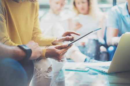 business idea: Closeup Young Woman Using Modern Tablet Hand.Hipster Working Great Business Idea Process.Coworkers People Gathered Together Decision Corporate Work.Startup Creative Presentation Concept Blurred