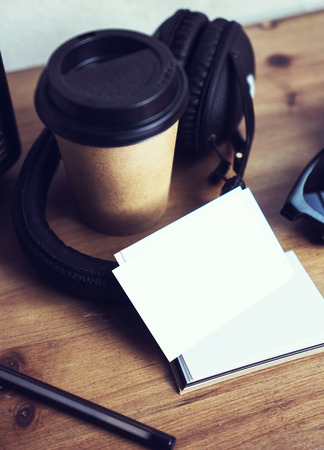 Closeup Stack Business Card White Paper.Blank Mockup Wood Table Background.Take Away Coffee Cup Coworking.Modern Headphones Portable Sunglasses Interior Cafe.Vertical Lifestyle Mock Up Objects