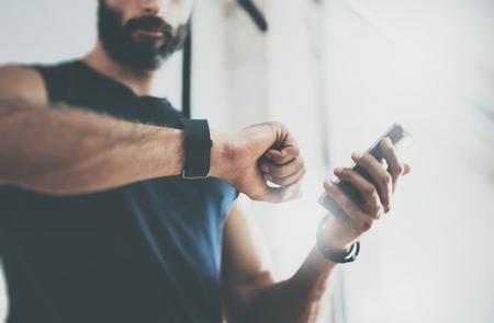 Toma en primer plano barbudo Deportivo hombre, tras los controles sesión de entrenamiento de fitness Resultados Smartphone.Adult tío con Sport Rastreador Muñequera Arm.Training duro dentro gym.Horizontal barra background.Blurred Foto de archivo
