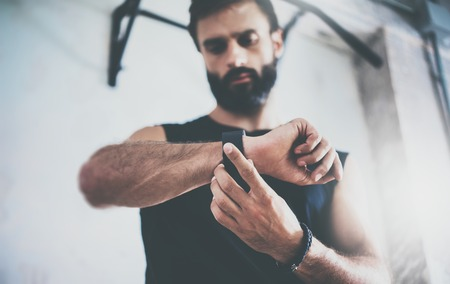 Close-up Shot Young Bearded Sportive Man After Workout Session Checks Fitness Results Smart Watch.Adult Guy Wears Sport Tracker Wristband Arm.Training hard gym.Horizontal bar background.Blurred