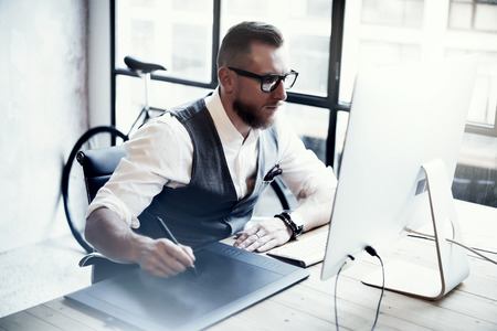 designer working: Bearded Creative Designer Working Drawing Digital Tablet Desktop Computer Wood Table.Stylish Young Man Wearing Glasses White Shirt Waistcoat Work Modern Loft Online Startup Project Blurred Stock Photo