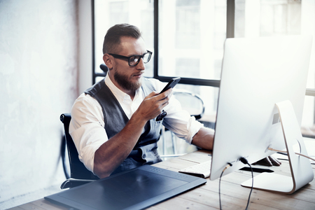 man working computer: Bearded Stylish Young Man Wearing Glasses White Shirt Waistcoat Working Modern Loft Startup Process.Creative Person Using Smartphone Texting Message.Drawing Tablet Desktop Computer Wood Table.Blurred