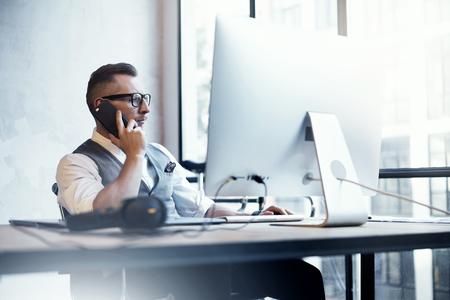 Uomo d'affari barbuto che indossa il gilet bianco della camicia che lavora il desktop moderno di partenza del sottotetto. Giovane creativo che usando il socio di riunione di chiamata di Smartphone. La strategia d'affari di pensiero dell'ufficio di lavoro del ragazzo. Archivio Fotografico - 64805326