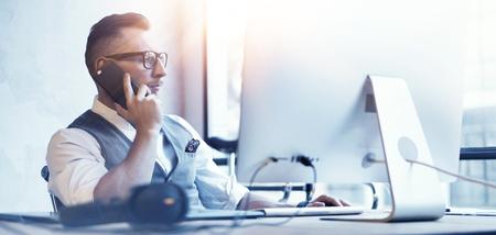 근접 촬영 수염 난 사업가 흰 셔츠를 입고 양복 조끼 작업 현대 로프트 시작 Desktop.Creative 젊은 남자가 스마트 폰 전화 회의 파트너 사용 .Guy 작업 사무