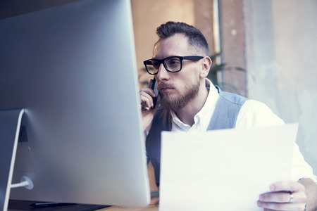 business decisions: Closeup Bearded Businessman Working Workplace Report.Man Using Smartphone Call Meeting Partner.Young Guy Wearing White Shirt Waistcoat Work Startup Desktop.People Make Great Business Decisions Office