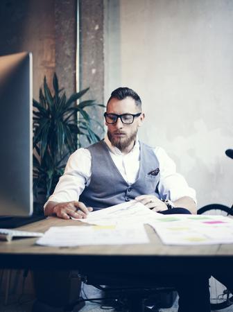 usando computadora: Elegante barbudo hombre joven con camisa blanca Vidrios Chaleco de trabajo moderno Loft Startup.Creative individuo que usa la computadora de escritorio de madera Tabla Workplace.Vertical borrosa Foto de archivo