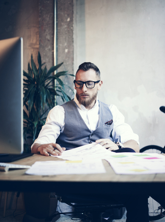 using computer: Stylish Bearded Young Man Wearing Glasses White Shirt Waistcoat Working Modern Loft Startup.Creative Guy Using Desktop Computer Wood Table Workplace.Vertical Blurred