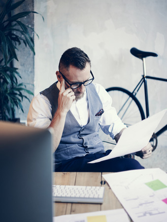 man shirt: Stylish Bearded Young Man Wearing Glasses White Shirt Waistcoat Working Modern Workplace Startup.Creative Guy Using Desktop Computer and Thinking Business Strategy Wood Table Office.Vertical Blurred Stock Photo
