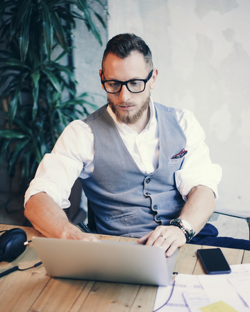 young guy: Bearded Businessman Wearing White Shirt Waistcoat Working Modern Studio Startup Project.Creative Young Guy Using Laptop Computer Wood Table.Work Process Workplace.Vertical Blurred