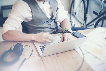 usando computadora: Closeup hombre de negocios barbudo vistiendo camisa blanca chaleco de trabajo Moderno inicio de la oficina Project.Creative Joven Guy utilizando ordenador portátil Wood Table.Work proceso Workplace.Horizontal borrosa