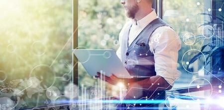 Concept Stratégie globale Virtual Icon Diagram Graph Interface Investissements Reserch.Bearded Businessman recherchant de grandes décisions d'affaires. Young Man Holding Laptop Hands Looking Panoramic Window.Wide