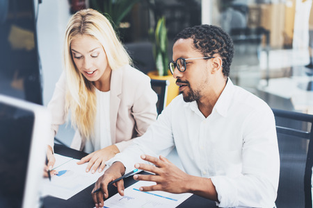 Zwei junge Mitarbeiter, die zusammen in einem modernen Büro arbeiten Bemannen Sie tragende Gläser und besprechen mit dem neuen Projekt der jungen Frau Horizontaler, unscharfer Hintergrund.