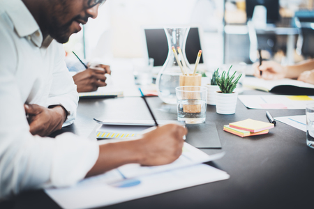 안경을 착용 하 고 현대 office.African 미국 남자에서에서 문서를 작성하는 흰 셔츠에 어두운 껍질 된 동료의 근접 촬영. 가로, 흐린 배경