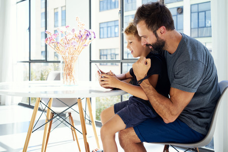 little boys: Young boy sitting with father at the table and playing together on pc tablet in modern apartment. Horizontal, blurred background