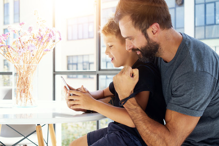 laptop home: Closeup of young boy and bearded man sitting at the table and playing together on pc tablet in modern apartment. Horizontal, blurred background