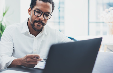 Dark skinned coworker wearing glasses and using laptop in modern office.African american man in white shirt working on workplace.Horizontal,blurred background. Stock Photo