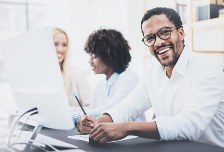 Dark skinned entrepreneur wearing glasses, working in modern office.African american man in white shirt smiling at the camera.Horizontal,blurred background.