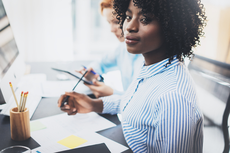 Young attractive african woman smiling and looking at the camera in modern office.Coworkers teamwork concept. Horizontal, blurred background Stock Photo