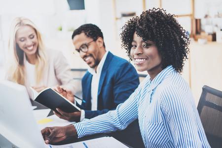 Grupo de tres compañeros de trabajo que trabajan juntos en proyecto de negocios en la oficina moderna. Joven mujer africana atractiva sonriendo, concepto de trabajo en equipo. Horizontal, fondo borroso Foto de archivo