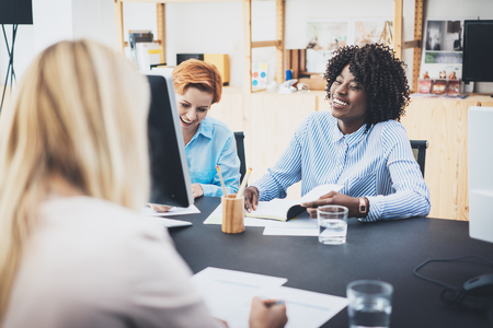 coworker: Beautiful womans laughing at business meeting in modern office. Group girls coworkers discussing together new fashion project. Horizontal, blurred background Stock Photo