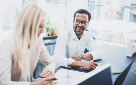 Two young coworkers working together in a modern office.Black man wearing glasses, looking at the camera and smiling.Woman discussing with colleague new project.Horizontal,blurred background.