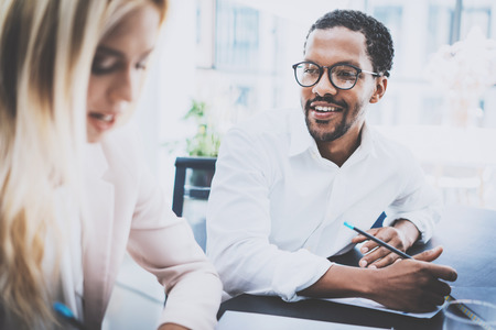 Two young coworkers working together in a modern office.Black man wearing glasses, looking at the businesswoman and smiling.Woman discussing with colleague new project.Horizontal,blurred background.