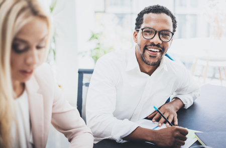 Two young business people working together in a modern office.Black man wearing glasses, looking at the camera and smiling.Businesswoman discussing with colleague new project.Horizontal,blurred Stock Photo