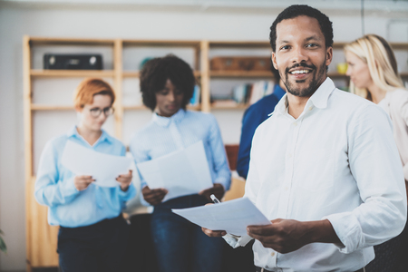 cuenta bancaria: African american entrepreneur in white shirt holding papers in hands and smiling at the camera.Teamwork concept in modern office. Horizontal,blurred background