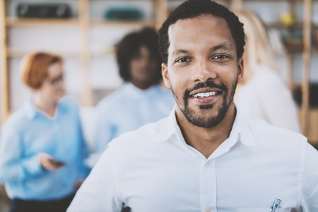 Portrait of african american man looking and smiling at the camera.Business team on the background in modern office. Horizontal,blurred background