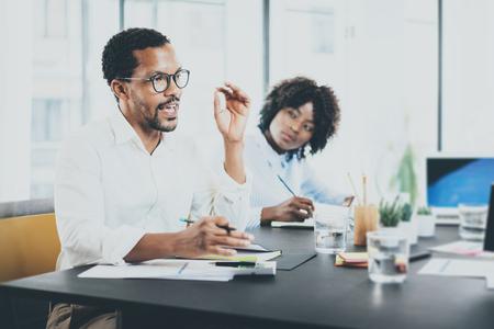 negras africanas: Negro director del proyecto africano explaning tarea de negocios en el cumplimiento de room.Two jóvenes empresarios que trabajan juntos en un office.Horizontal moderna, fondo borroso Foto de archivo