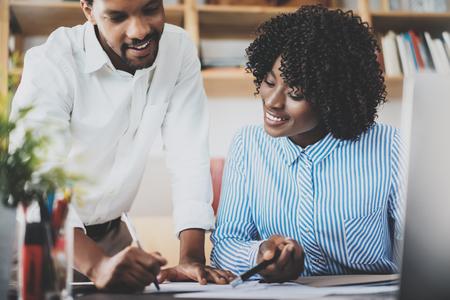 モダンなオフィスで一緒に働く若い同僚。黒のビジネスの人々 は、新しいスタートアップ プロジェクトについて議論します。水平、ぼやけ 写真素材