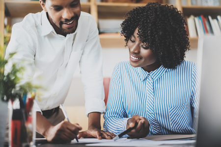 Two young coworkers working together in a modern office.Black business people discussing new startup project.Horizontal,blurred