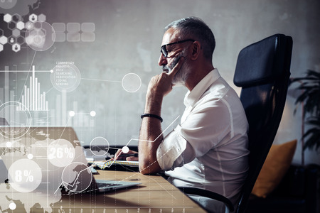 Concept of adult bearded businessman making a great business decisions in modern workplace.Screen of global virtual icon,diagram and graph interfaces.Horizontal Blurred