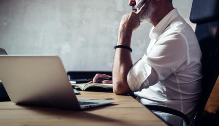 empleado de oficina: Adulto barba empresario que usan gafas clásicas y de trabajo en la mesa de madera en primer plano loft.Horizontal moderna, fondo borroso