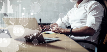 Concept of adult bearded businessman searching a great business solutions in modern workplace.Screen global virtual icon,diagram and graph interfaces.Horizontal wide, blurred