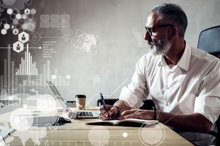 Concept of digital screen with global virtual icon,diagram, graph interfaces.Adult successful businessman wearing a classic glasses and working with laptop at the wood table in modern loft.Horizontal