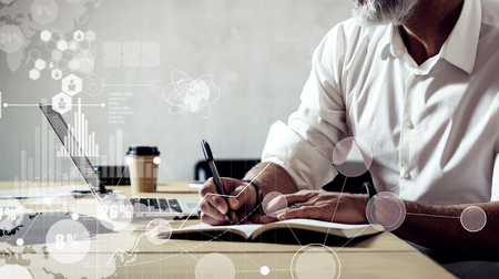 Concept of digital screen with global virtual icon,diagram, graph interfaces.Adult successful businessman wearing a classic glasses and working on laptop at the wood table in modern loft.Wide Reklamní fotografie