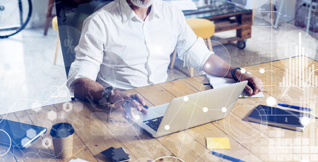 Concept of digital screen with virtual icon,diagram, graph and interfaces.Stylish bearded middle age man using laptop on workplace. Horizontal wide, blurred background