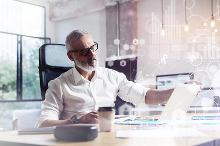 가상 아이콘, 다이어그램, 그래프와 인터페이스 디지털 화면의 개념. 현대 전문 스튜디오에서 나무 테이블에서 작업하는 클래식 안경을 착용하는 전문 스톡 콘텐츠