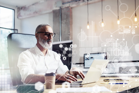Concept of digital screen,virtual icon,diagram, graph and interfaces.Middle age financial analyst wearing a classic glasses and working at the wood table with exchange markets.Horizontal Archivio Fotografico