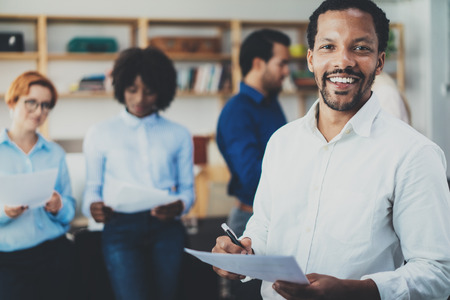 Teamwork concept in modern office.Young african businessman wearing white shirt holding papers at hands and standing front of the coworkers team.Horizontal,blurred background