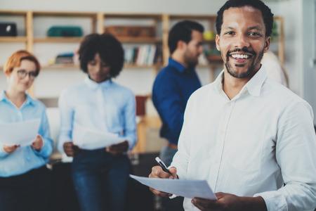 Teamwork-Konzept in modernen office.Young afrikanischen Geschäftsmann mit weißen T-Shirt halten Papiere an den Händen und stehend vor der Mitarbeiter team.Horizontal, unscharfen Hintergrund