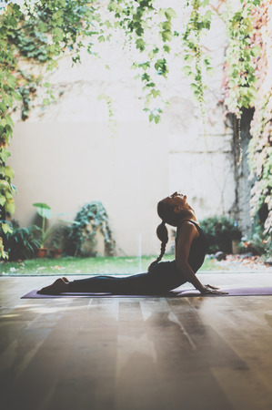 Portrait of gorgeous young woman practicing yoga indoor. Beautiful girl practice cobra asana in class.Calmness and relax, female happiness.Vertical, blurred background