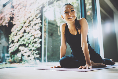 Portrait of gorgeous young woman practicing yoga indoor. Beautiful girl smiling during practice class.Calmness and relax, female happiness concept.Horizontal, blurred background