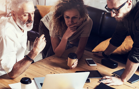 Closeup concept of business people brainstorming.Bearded man talking with account director and creative manager to finding great work solution.Horizontal, blurred background