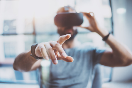 Closeup of male hand.Bearded young man wearing virtual reality goggles in modern coworking studio. Smartphone using with VR headset in office. Horizontal, blurred Reklamní fotografie - 65933571