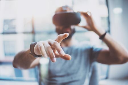 El primer del varón hand.Bearded hombre joven que llevaba gafas de realidad virtual en el estudio de coworking moderna. Smartphone mediante la realidad virtual en el cargo auricular. Borroso Foto de archivo
